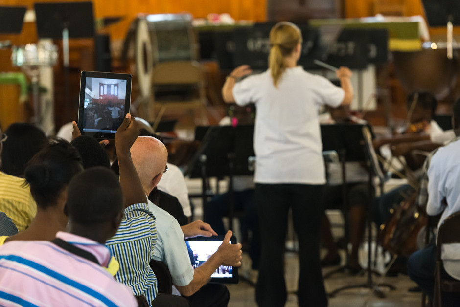 The camp orchestra plays during the weekly concert, as onlookers capture the action with modern technology.