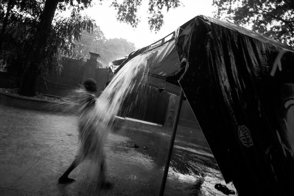 A child knocks water out of a tarp covering a tent at Zanmi Lasante during a rainstorm.